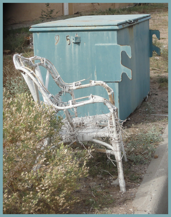 white chair by trash dumpster